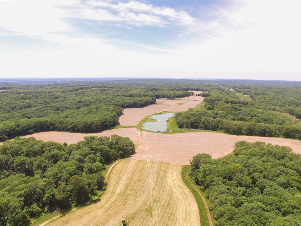 aerial view of tillable acreage, large lake and woods.